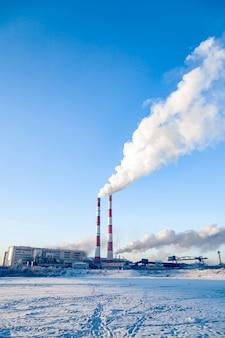 工場のパイプの煙が街の雰囲気を汚しています。石油、石炭、ガス処理、環境汚染、水資源への排出、腫瘍性疾患、がんの概念