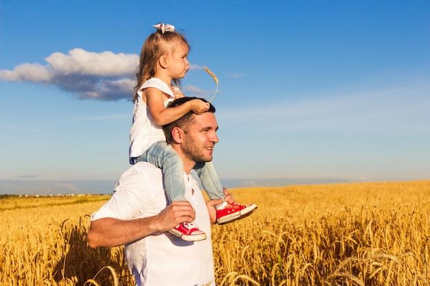 Счастливая семья. папа и дочь, сидящие на его плечах, стоят посреди пшеничного поля в солнечный летний день