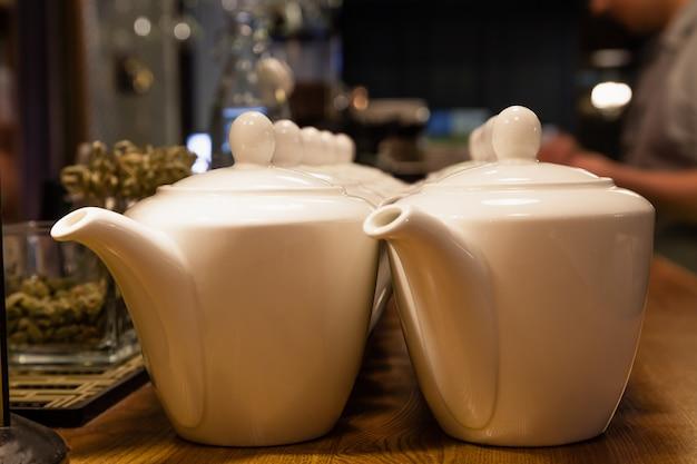 Многие белые керамические чайники с круглыми крышками стоят на деревянной барной стойке в ресторане. концептуальные блюда в кафе, чай, завтрак