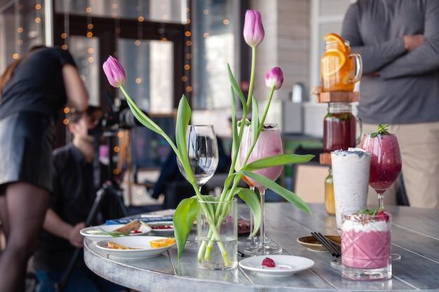 フードスタイリストとカメラマンが飾って、テーブルでさまざまなカクテル、ミルクセーキ、スムージー、花チューリップの花瓶を撮影する準備をします。