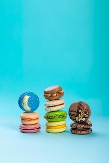 青色の背景にカラフルな甘いマカロンデザートの種類