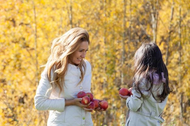 美しい母と娘が熟した赤いリンゴで遊ぶ