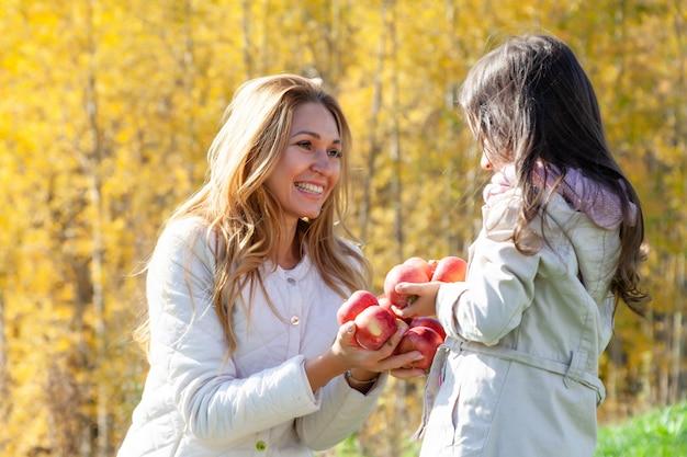 美しい母親、娘は赤いリンゴで遊ぶ