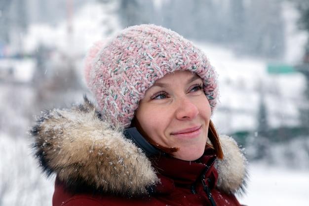 暖かいジャケット屋外でポンポンとピンクのニット帽子で横に探している若い美しい笑顔の女性