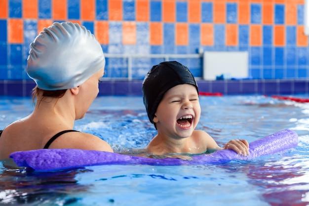 Улыбающаяся мама в чёрном купальнике и серебряной резиновой шапке учит плавать сына