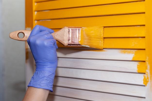 黄色のペンキ、創造的なデザインの家の改修をテーマにした自然な木製のドアをペイントペイントブラシで紫色のゴム手袋で女性のクローズアップ手。木製の表面をペイントする方法。選択したフォーカス
