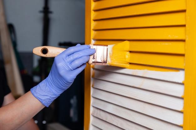 黄色いペンキで自然な木製のドアをペイントペイントブラシで紫色のゴム手袋で女性の手をクローズアップ。創造的なデザインの家のインテリア。木製の表面をペイントする方法。選択したフォーカス