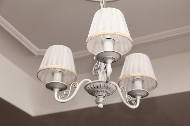 Люстры с тремя электрическими лампами и абажурами, висящими на потолке