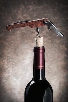 ワインの瓶のクローズアップのコルクせん抜き