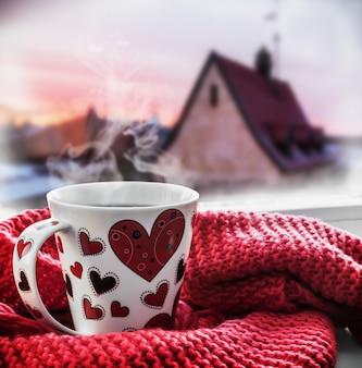 Чашка с горячим напитком на подоконнике
