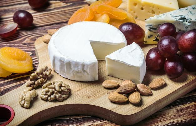 フルーツと木製のテーブルのブドウとチーズの品揃え