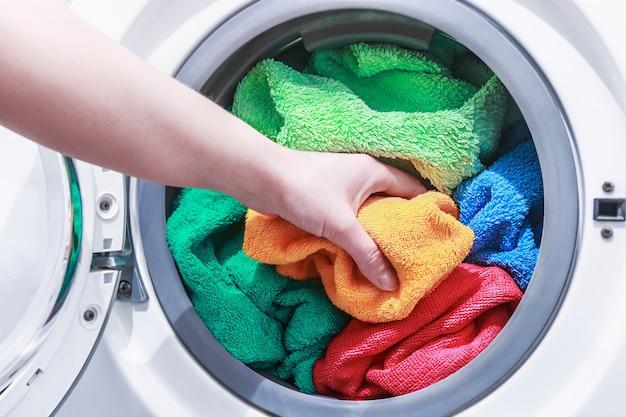 手で洗濯機に洗濯物を入れます