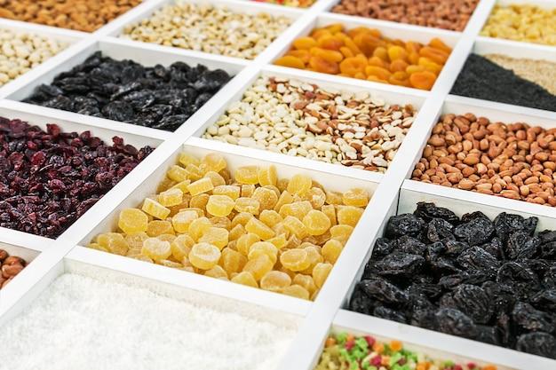 Различные орехи, сухофрукты и ягоды в деревянной коробке