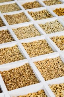 Различные цельные и молотые орехи в деревянном ящике