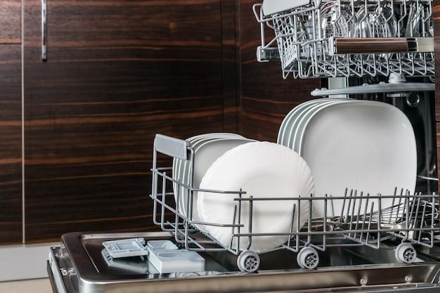 Чистая посуда, бока и столовые приборы в посудомоечной машине