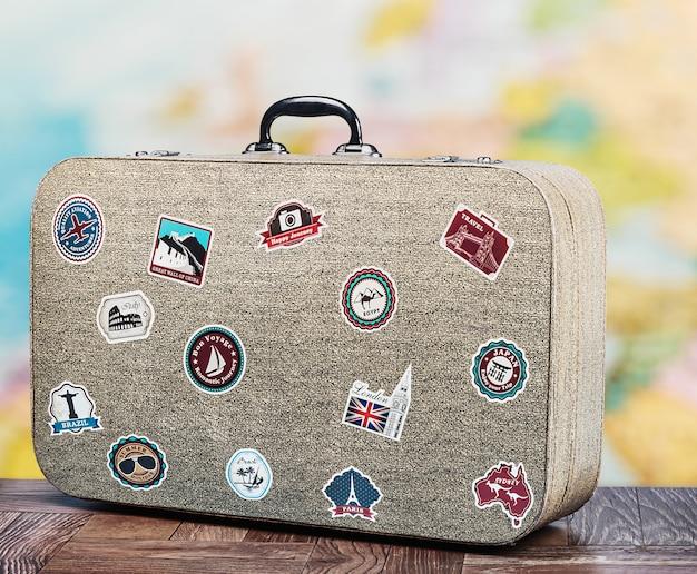 床にスティッカーが付いている古いスーツケース