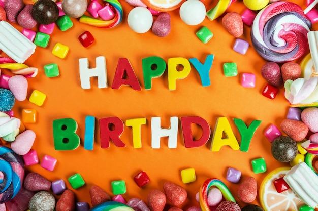 お菓子だらけの背景にお誕生日おめでとう