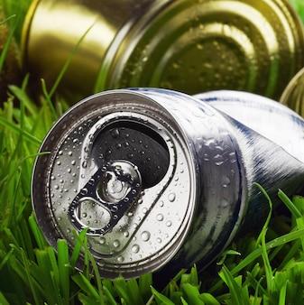 Мусор из старых алюминиевых банок на траве