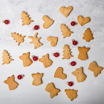 Рассеяние рождественского печенья на серой поверхности. плоская планировка. вид сверху. рождество и новый год концепция. готовка