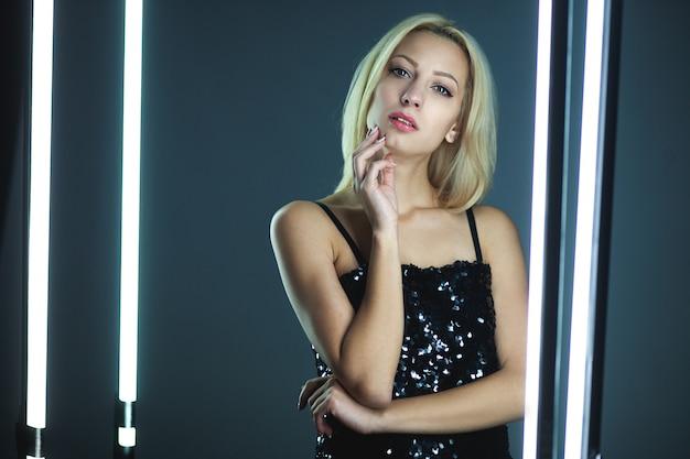 暗いインテリアに立っているエレガントな黒のスパンコールストラップキャミドレスを着ている金髪の女性