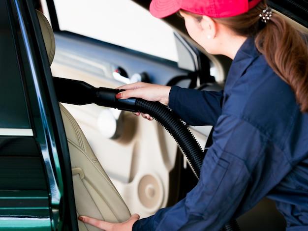 ガレージで車の座席を掃除作業員のアジア人女性を閉じます。