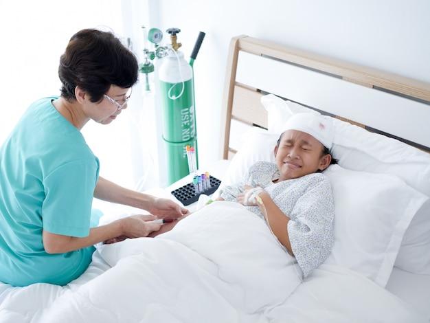 病院の部屋でベッドに横たわっているアジア人少女に注射をやり直す上級看護師。