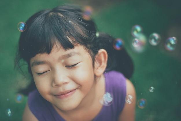 閉じた目とシャボン玉を持つ少女