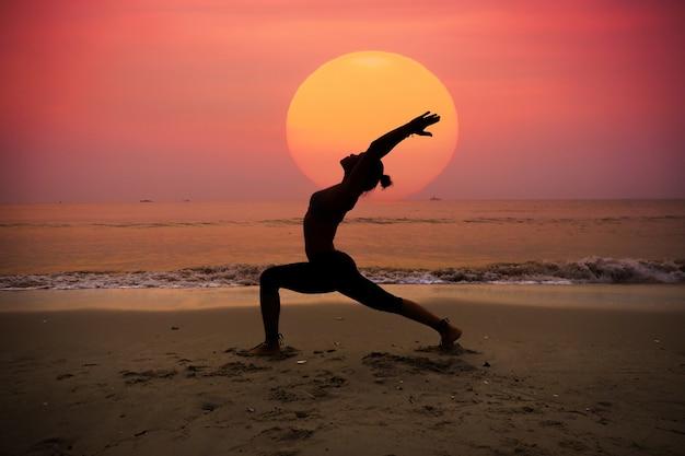 Женщина практикует йогу с солнцем позади нее