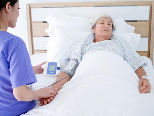 Пожилая женщина, лежащая в больничной койке.