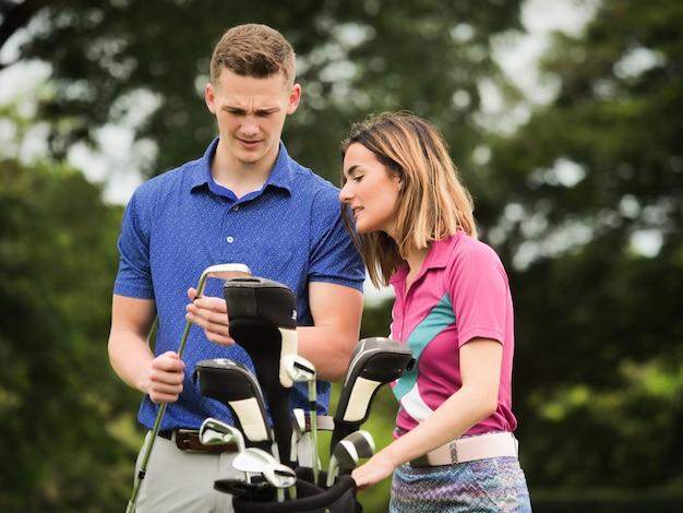 カップルのゴルフコンセプト:若い男が彼の女の子の友人にゴルフを教える