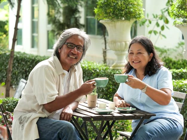 庭のコーヒーを飲んでいる間に笑っているシニアカップル。