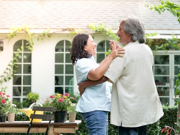 家庭庭で一緒に笑っているシニアカップル。