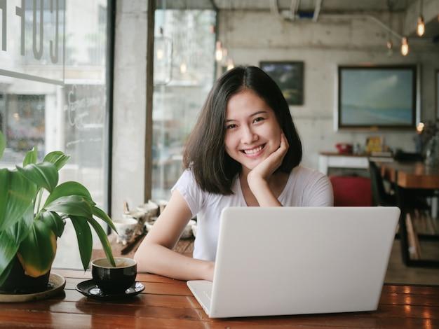 アジアの女性がコーヒーを飲むとコーヒーショップカフェでリラックス