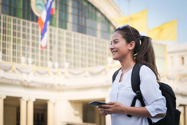 Азиатская женщина, путешествующая с мобильным телефоном