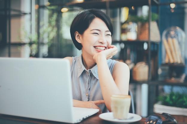 Женщина улыбается с кофе и ноутбуком