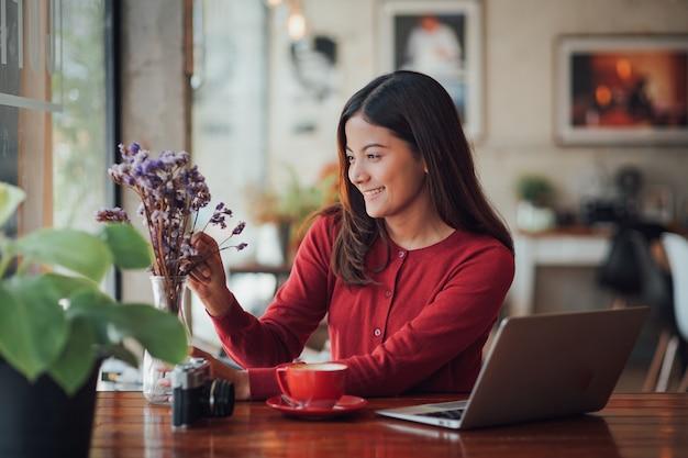 Азиатская девушка дела работая и выпивая кофе в кафе с компьтер-книжкой
