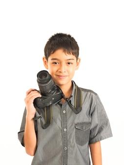 白い背景の上のデジタル一眼レフカメラでアジアの少年