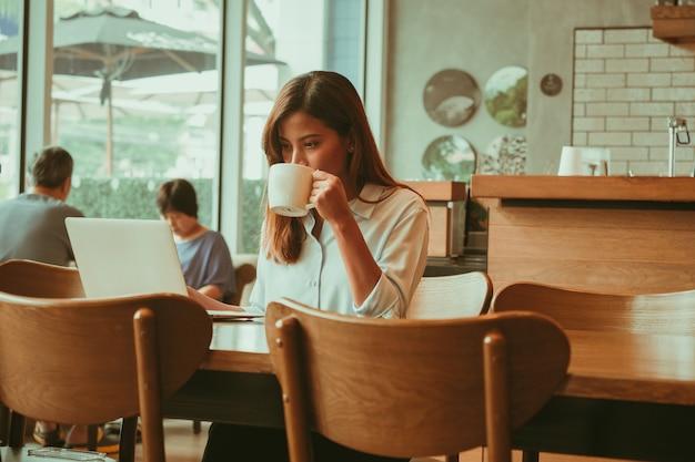 アジアの女性がコーヒーショップカフェでノートパソコンでの作業