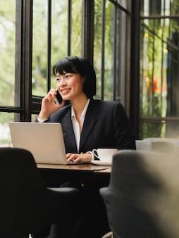 アジアの女性のラップトップを使用してコーヒーショップカフェでコーヒーを飲む