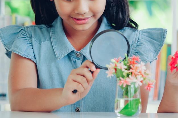 虫眼鏡を手で保持しているかわいい女の子。