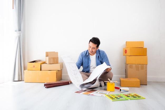 Азиатский мужчина дизайн и думать, чтобы украсить дом