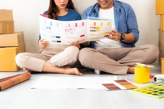 Азиатский мужчина объявление женщина дизайн и думать, чтобы украсить дом