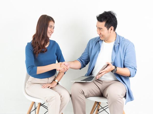 Азиатские мужчина и женщина разговаривают с ноутбуком для бизнеса на белом фоне