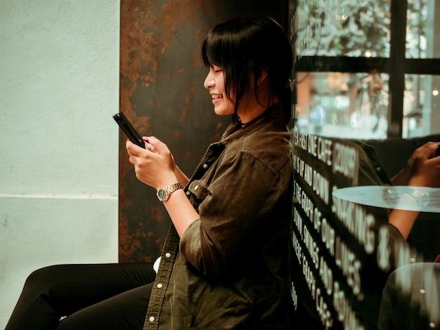 Азиатская женщина пьет кофе в кафе