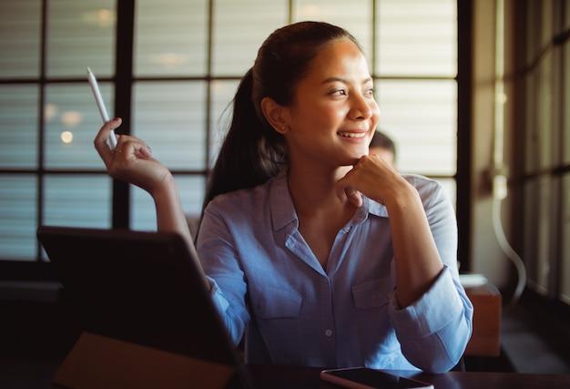 アジアの女性がコーヒーを飲むと、カフェでラップトップコンピューターでの作業