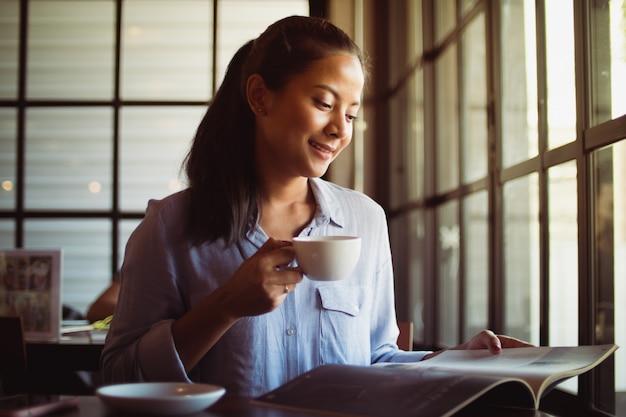 アジアの女性がカフェでコーヒーを飲む