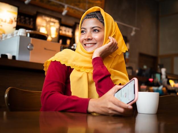 Портрет молодой мусульманской женщины в кафе
