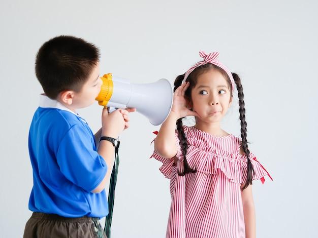 アジアのかわいい男の子とメガホン歌を持つ少女