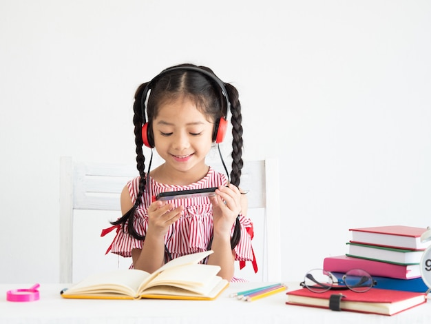 机の上の本とアジアのかわいい女の子