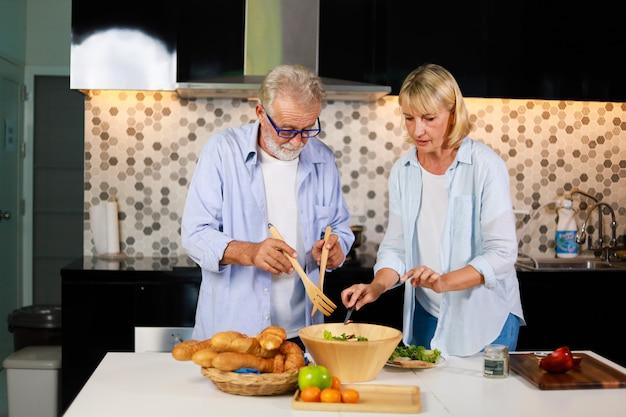 年配のカップル男と女の台所で幸せな気分で調理